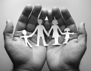 Due mani aperte che sorreggono sagome di una famiglia ritagliata nella carta